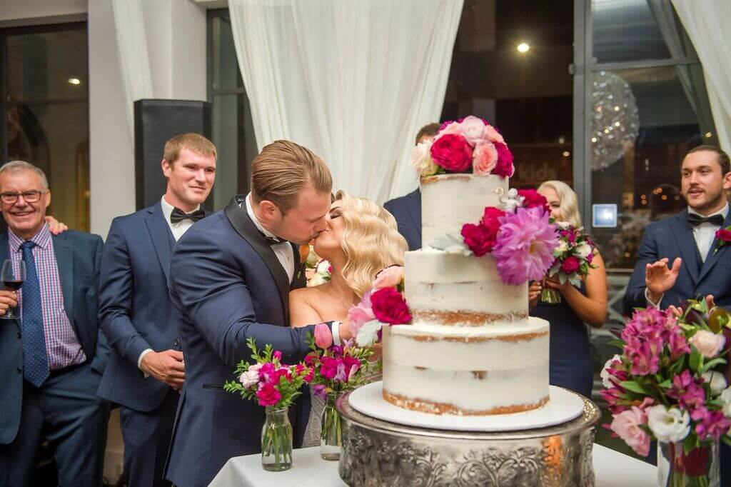 Bridal couple cutting three tier wedding cake, wedding reception venue Hotel Richmond, photo by Ky Luu